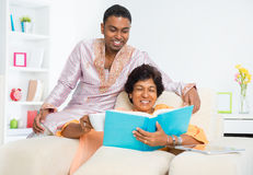 Indian family reading a book. Mature 50s Indian women reading a book with her son at home Royalty Free Stock Images