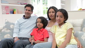 Indian Family Sitting On Sofa Watching TV Together stock footage