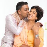 Indian family, son kissing mother. Portrait of happy Indian family at home. Indian 30s grown son kissing his mature 50s mother Royalty Free Stock Photos