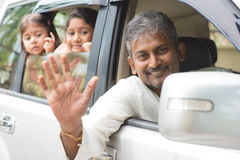 Indian family waving hands in car. Indian family waving hands and saying goodbye, sitting in car ready to trip. Asian family lifestyle stock photos