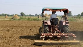 A Indian Farmer is cultivation a field with his tractor, making it ready to sow the seeds stock photos