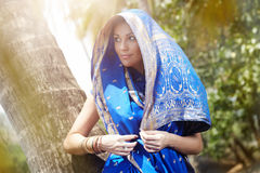 Indian fashion. Elegant lady in blue Indian sari standing at the palm in wild jungle. Natural sunlight and colors Royalty Free Stock Image