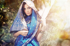 Indian fashion in sari. Beautiful lady outdoors in the stylish sari posing in the wild jungle under the summer sunshine royalty free stock images