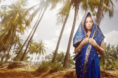 Indian fashion in sari. Beautiful lady outdoors in stylish sari standing in the wild jungle. Artistic colors added royalty free stock images