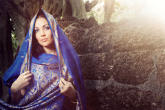 Indian fashion in sari. Beautiful lady outdoors in elegant sari near the old stony wall. Horizontal portrait stock photo