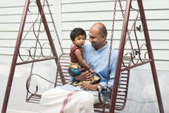 Indian father and daughter outdoor. Indian parent and child sitting on a swing. Traditional India family outdoor portrait Stock Photo