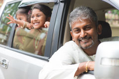 Indian father driving new car. Indian family sitting in car ready to trip. Asian parent and children lifestyle stock photo