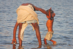 Indian Father washing his child Stock Photos