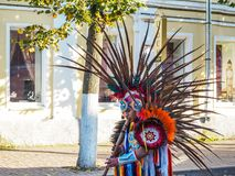Indian with feathers on his head plays the flute. Russia. Saint-Peterburg. Autumn 2017. stock photos