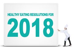 Indian female chef pushing a big billboard. Photo of Indian female chef wearing uniform and pushing a big billboard with a text of healthy eating resolutions for Stock Photos