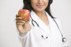 Indian female doctor showing red apple focus on apple Stock Photo
