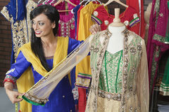 Indian female dressmaker measuring traditional outfit at design studio Stock Photos