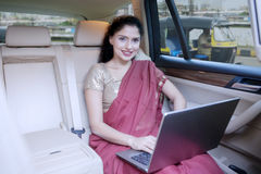 Indian female entrepreneur with laptop in car Royalty Free Stock Image