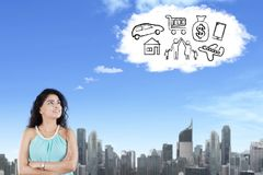 Indian female student imagining her wishes. Portrait of Indian female student imagining her wishes while looking at cloud speech bubble in the sky Stock Photos