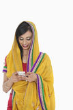 Indian female in traditional wear using cell phone over white background Royalty Free Stock Photo