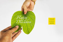 Indian festival dussehra, showing golden leaf with traditional indian sweets pedha in silver bowl on yellow background, greeting c. Ard Stock Image