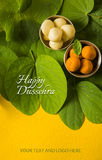Indian festival dussehra, showing golden leaf with traditional indian sweets pedha in silver bowl on yellow background, greeting c Royalty Free Stock Photo