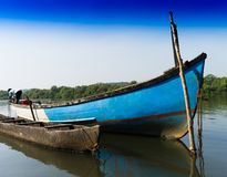 Indian fisherman in his boat background. Goa river forest jungle south horizontal orientation nobody blank empty space sparse vivid vibrant bright color rich royalty free stock images