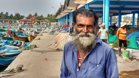 Portrait of old fisherman at harbour. An Indian fisherman is posing in front of colorful fishing boats and nets in harbour of Kannur, Kerala, India Royalty Free Stock Image