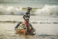 Indian Fisherman. Pulling his fishing boat to sea sore with full of fish,captured from sea Stock Image