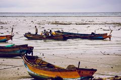 Indian fishermen on the beach with their boats stock images