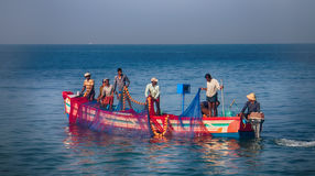Indian fishermen graphically pull painted Seine right in boat 2. royalty free stock image