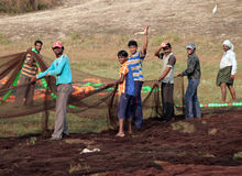 Indian fishermen are laying out on the ground fishing nets for drying Royalty Free Stock Images