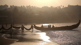 Indian fishermen in silhouette at sunrise stock video footage