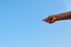 Indian flag kite with hand holding it. Kite Indian flag in blue sky with hand stock photo