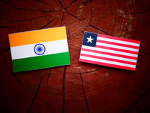 Indian flag with Liberian flag on a tree stump isolated. Indian flag with Liberian flag on a tree stump Royalty Free Stock Images