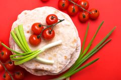 Indian flatbread chapati, green onion, cherry tomato. Color surge trend. Traditional Kerala Indian cuisine. Homemade flatbread chapati with green onion and stock photos