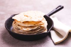 Indian flatbread chapati, green onion. Color surge trend. Traditional Kerala Indian cuisine. Homemade flatbread chapati on gray slate background. Copyspace stock photos