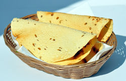 Indian Poppadums. Folded Indian Papadums or Poppadums in wicker basket on table Stock Images