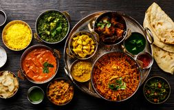 Indian food Curry butter chicken, Palak Paneer, Chiken Tikka, Biryani, Vegetable Curry, Papad, Dal, Palak Sabji, Jira Alu. Rice with Saffron on dark background royalty free stock images