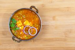 Indian Food or Indian Curry in a copper brass serving bowl. Indian Food or Indian Curry or Matar Paneer in a copper brass serving bowl lying on wooden surface stock image