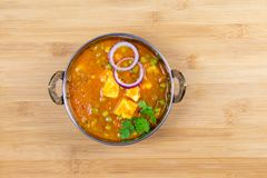 Indian Food or Indian Curry in a copper brass serving bowl. Indian Food or Indian Curry or Matar Paneer in a copper brass serving bowl lying on wooden surface stock photography