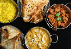 Indian Food Curry Meal Dishes. Chicken passanda, lamb rogan josh with pilau rice, naan bread and samosas Stock Images