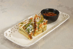 Indian Food Dhokla topped with sesame seeds and green chilly Stock Image