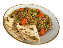 Indian Food Keema and Chapatis. A plate of beef or lamb curry with peas and cherry tomatoes and chapatis, isolated on white, and with clipping path included Stock Photo