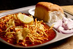 Indian Food - Maharashtrian Misal Pav. Spicy Maharashtrian curry usually consumed with a bread, onion and a squeeze of lemon. Close Up Royalty Free Stock Photography