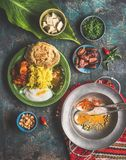 Indian food meals in bowls served with banana leaf: Curry, butter chicken, rice, lentils, paneer, samosa, naan, chutney, spices. Royalty Free Stock Images