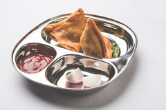 Indian food snack Samosa served in a stainless steel plate with tomato ketchup Royalty Free Stock Photos