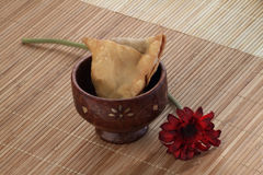 Indian Food Spicy Samosa with a flower on wooden background Royalty Free Stock Photography