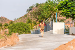 An Indian girl with a backpack walks down the street. Back view. Copy space for text. Stock Photography