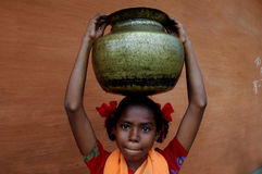 Indian girl carrying water. A young Indian girl is carrying a heavy big pitcher of drinking water on her head in rural India Stock Images