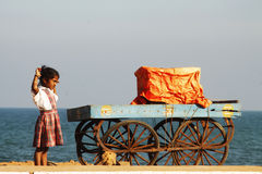 Indian girl with cart on the beach. Small indian school girl with cart on the beach in Pondicherry Royalty Free Stock Images