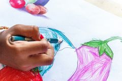 An Indian girl child seen drawing. And coloring using color pencils. With selective focus on the subject stock photos