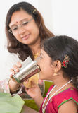 Indian girl drinking water. Indian family dining at home. Photo of child drinking water on dining table. Traditional home cook meal stock photo