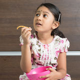 Indian girl eating cookie Stock Photos