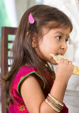 Indian girl eating snack. Indian family dining at home. Candid photo of Asian child self feeding snack papadum. India culture stock photos